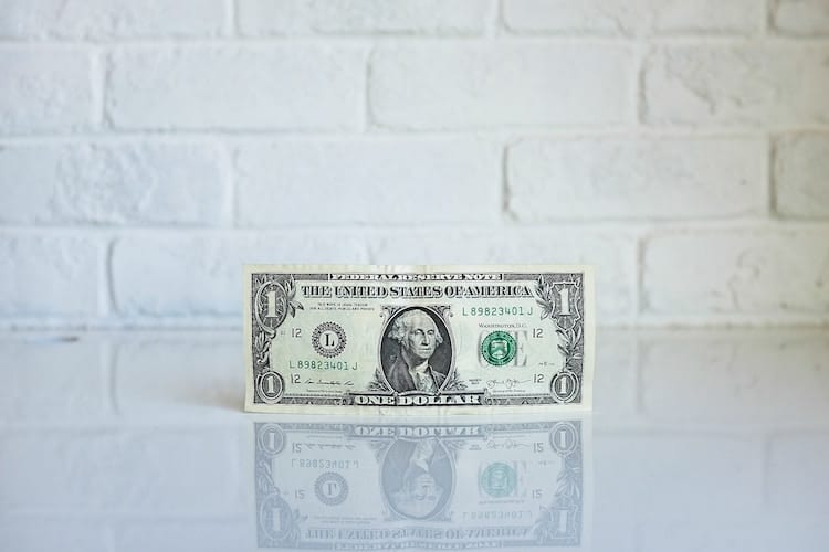 A $1 bill in front of a white wall, on a white table