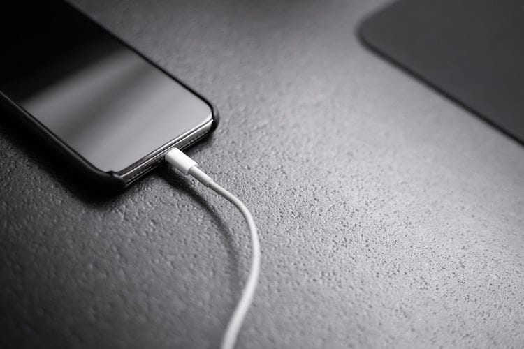 A black iPhone charging on a desk