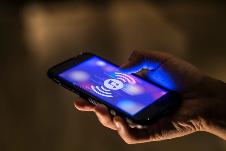 Hand holding a smartphone playing music in dim lighting