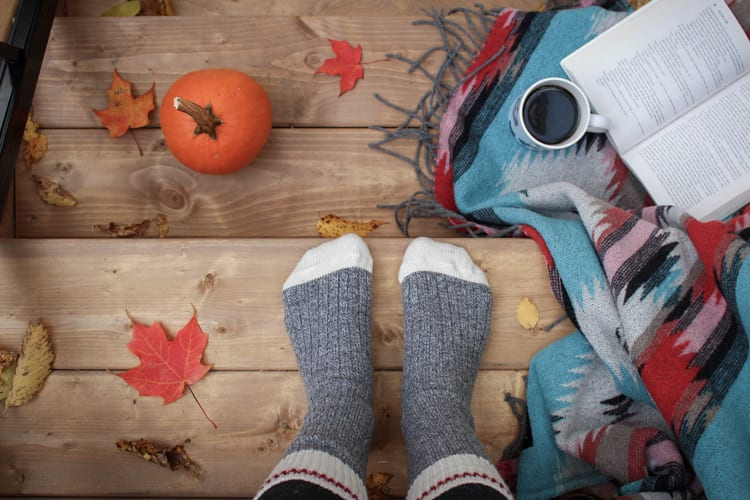 Pair of feet in cozy grey socks with fall decor around including pumpkin and coffee