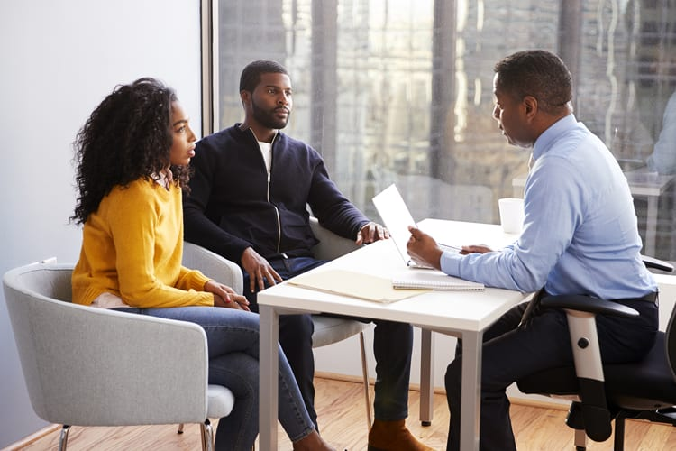 Black couple meeting with a financial advisor at an office